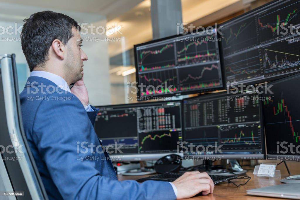 Effectenmakelaar handel online kijken naar grafieken en data analyses op meerdere computerschermen. foto