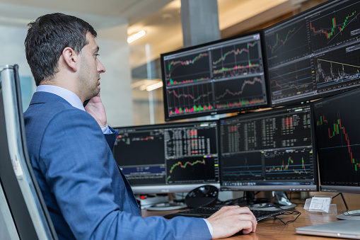 Stock Broker Trading Online Watching Charts And Data Analyses On Multiple Computer Screens Stock Photo - Download Image Now