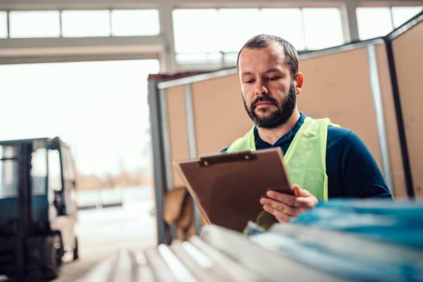 lagerbearbeiter prüft lagerinventar in der lagerfabrik - papierrollenhalter stock-fotos und bilder