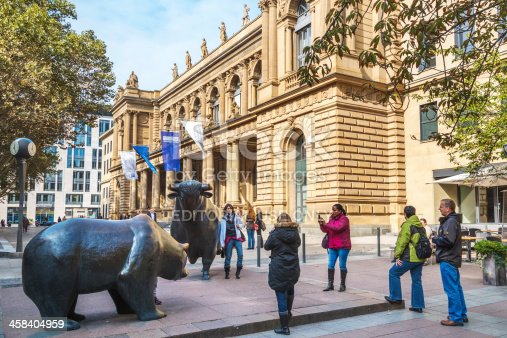 Frankfurt, Germany - October 1, 2013: Main entrance of the Frankfurt stock exchange of the Deutsche Boerse AG. The historic building is located in the city center. Tourists Taking Photographs Of Each Other with the Bull & Bear in front of the Exchange.