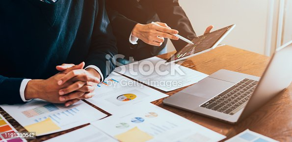 Stock exchange market concept, business team trader looking on tablet and laptop with graphs analysis candle line in office room, diagrams on screen.