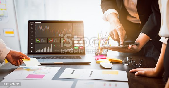 Stock exchange market concept, business teamwork brainstorming Meeting and looking on computer with graphs analysis candle line on table in night office, diagrams on screen.