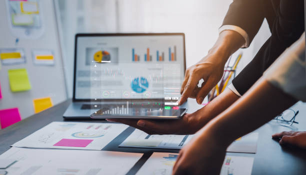 Stock exchange market concept, businessman trader holding tablet with graphs analysis candle line on table in office, diagrams on screen. stock photo