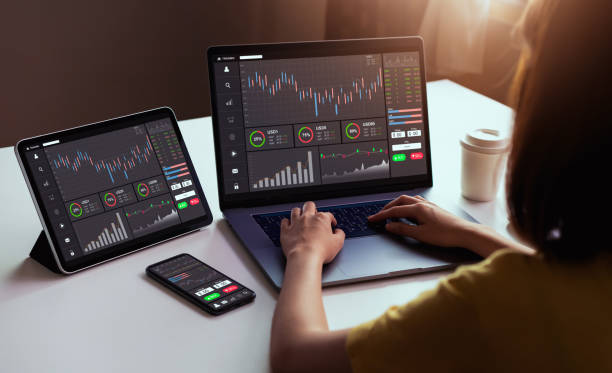 stock exchange market concept, businesswoman trader looking on laptop and tablet, smartphone with graphs analysis candle line in office room, diagrams on screen. - scambio commerciale foto e immagini stock