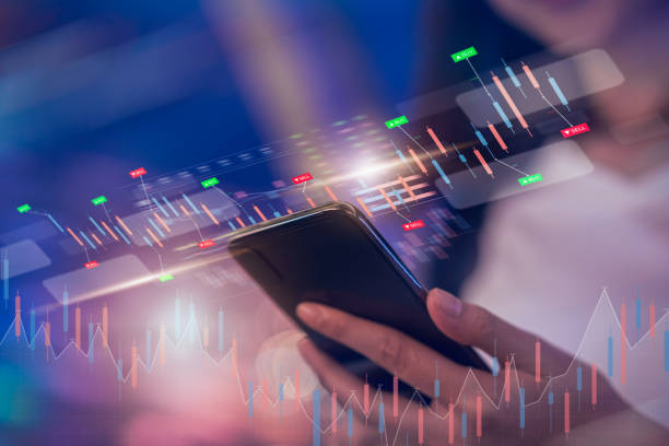 Stock exchange market concept, businesswoman trader looking on smartphone with graphs analysis candle line on bokeh colors light in night atmospheric city. stock photo
