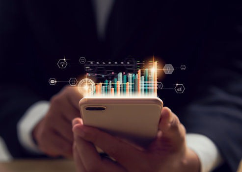 Stock exchange market concept, hand trader holding smartphone with graphs analysis candle line on bokeh colors light in night.