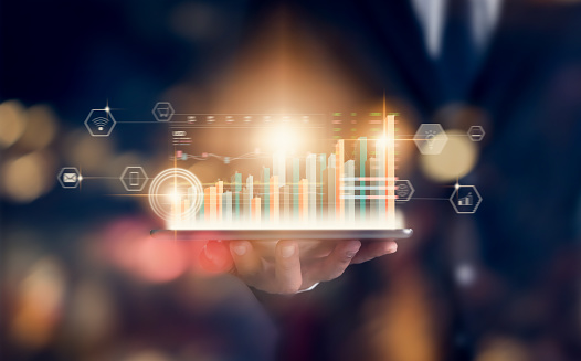 1044507110 istock photo Stock exchange market concept, hand trader holding tablet with graphs analysis candle line on bokeh colors light in night. 1186684203