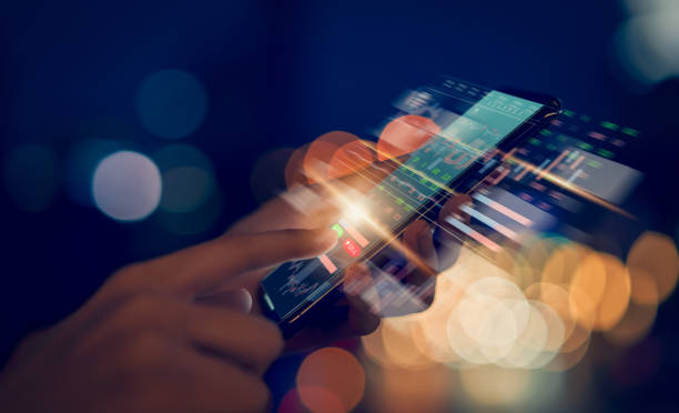 Stock exchange market concept, hand trader touching on smartphone with graphs analysis candle line on bokeh colors light in night atmospheric city. stock photo
