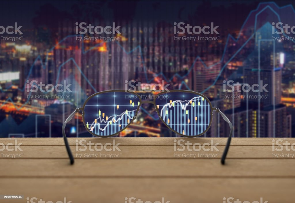 Stock exchange market trading graph focused in glasses lenses on the wooden over the abstract photo blurred of trading graph background, business technology trading concept stock photo