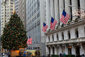 """New York, USA - December 27, 2011: The New York Stock Exchange at Wall Street with the American flags at the 1903 historic building and the famous Christmas tree in front of the building during the Christmas Holiday season."""
