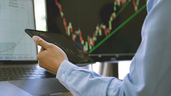 stock exchange trader working  with graphs, diagrams on monitor in modern trading office.