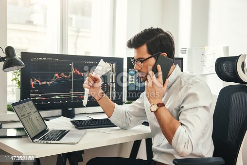 istock Stock falling. Shocked bearded businessman or trader in formalwear and eyeglasses is talking with client by smartphone and feeling nervous while sitting in modern office. 1147352158
