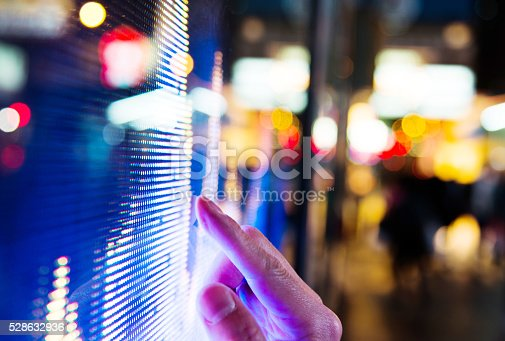 Man finger pointing at LED screen of stock market price at night.