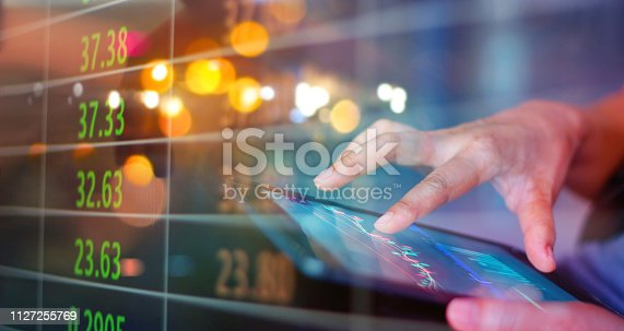 istock Stock market. Businessman using a mobile device to check market data and currency exchange rates on colorful background. 1127255769