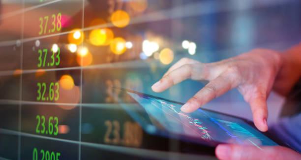Börse. Geschäftsmann nutzt ein mobiles Gerät, um Marktdaten und Wechselkurse auf bunten Hintergrund zu überprüfen. – Foto