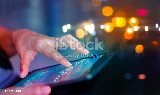 865596966istockphoto Stock market. Businessman using a mobile device to check market data and currency exchange rates on colorful background. 1127256103