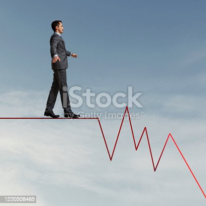 Businessman on business graph falling down. Recession concept.