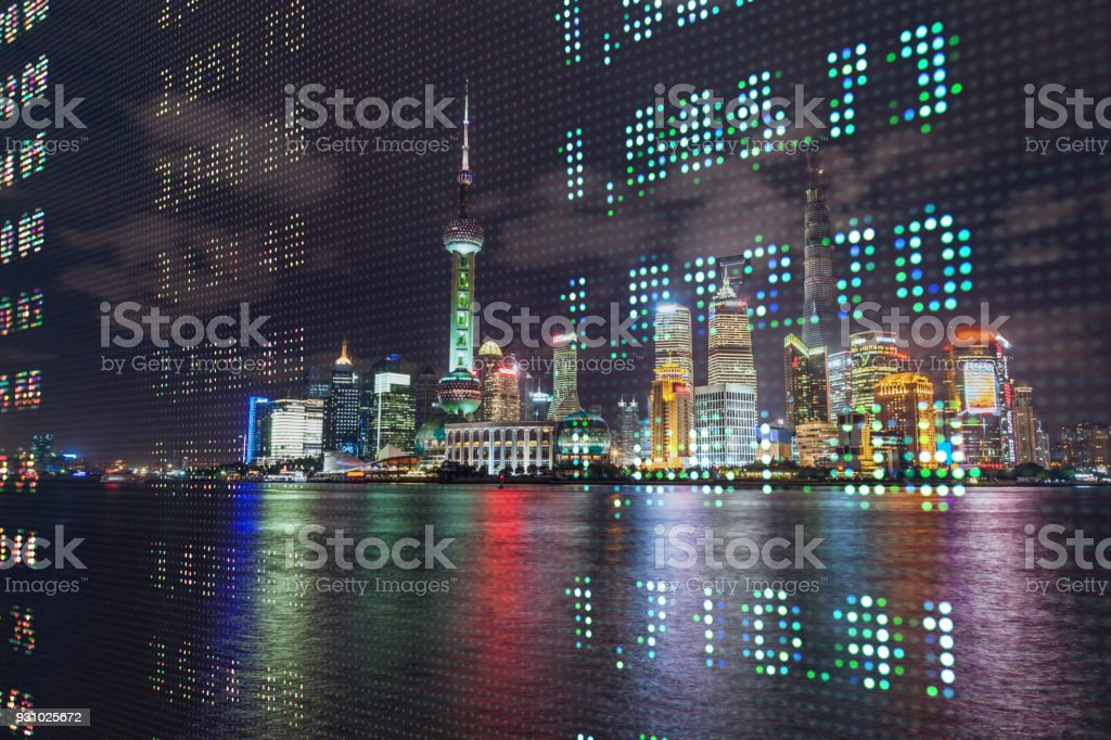 stock market data in the trading board with Shanghai night scence in the background stock photo