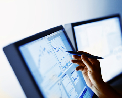 Hand pointing to stock market chart.