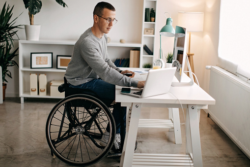 Young man with disabilities working on his stock market portfolio