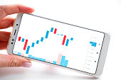 istock Stock market or forex trading graph and candlestick chart on mobile device in businessman hand. Economy trends idea. Online finance trading, financial investment concept. On white 1188486468