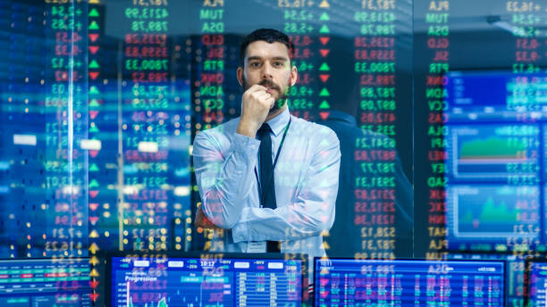 Stock Market Top Trader Looks at Projected Ticker Numbers and Graphs Running, Analysing Data to Make Best Sell. Behind Him Room Full of Screens and Statistics. stock photo