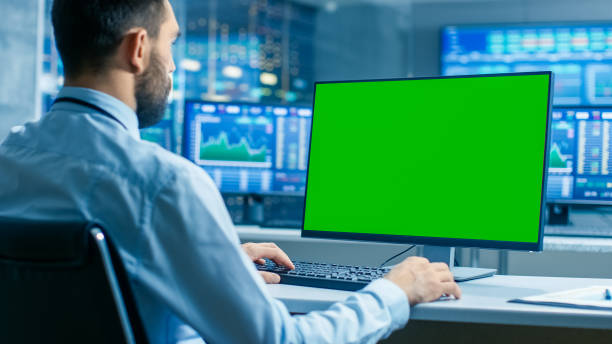 Stock Market Trader Working on a Computer with Isolated Mock-up Green Screen. In the Background Monitors Show Stock Ticker Numbers and Graphs. Stock Market Trader Working on a Computer with Isolated Mock-up Green Screen. In the Background Monitors Show Stock Ticker Numbers and Graphs. looking over shoulder stock pictures, royalty-free photos & images