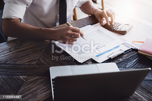 istock Stock marketing analysis concept, Male using calculator and computer laptop  to analyze stock market chart data application in office. 1153554487