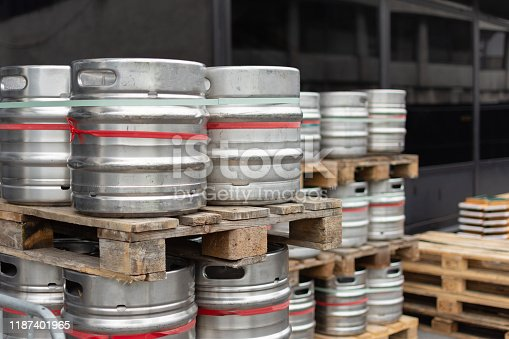 istock Stock of steel beer kegs on the wooden palettes. Many beer barrels at a beer factory. 1187401965