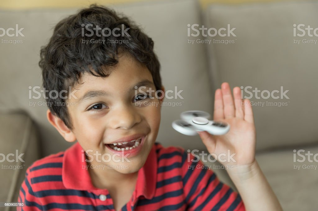 Stock Foto av en vacker glad pojke med en Fidget Spinner bildbanksfoto