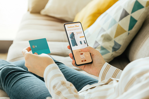 Stock photo of a woman buying a dress online with the phone and a credit card from the sofa at home. E-commerce concept