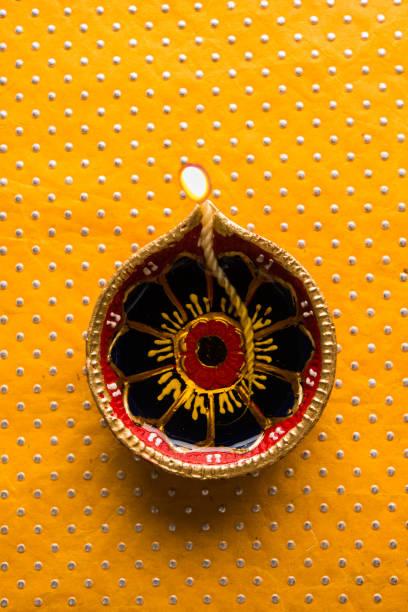 stock photo of beautiful diwali diya, isolated over decorative background, moody lighting and selective focus stock photo