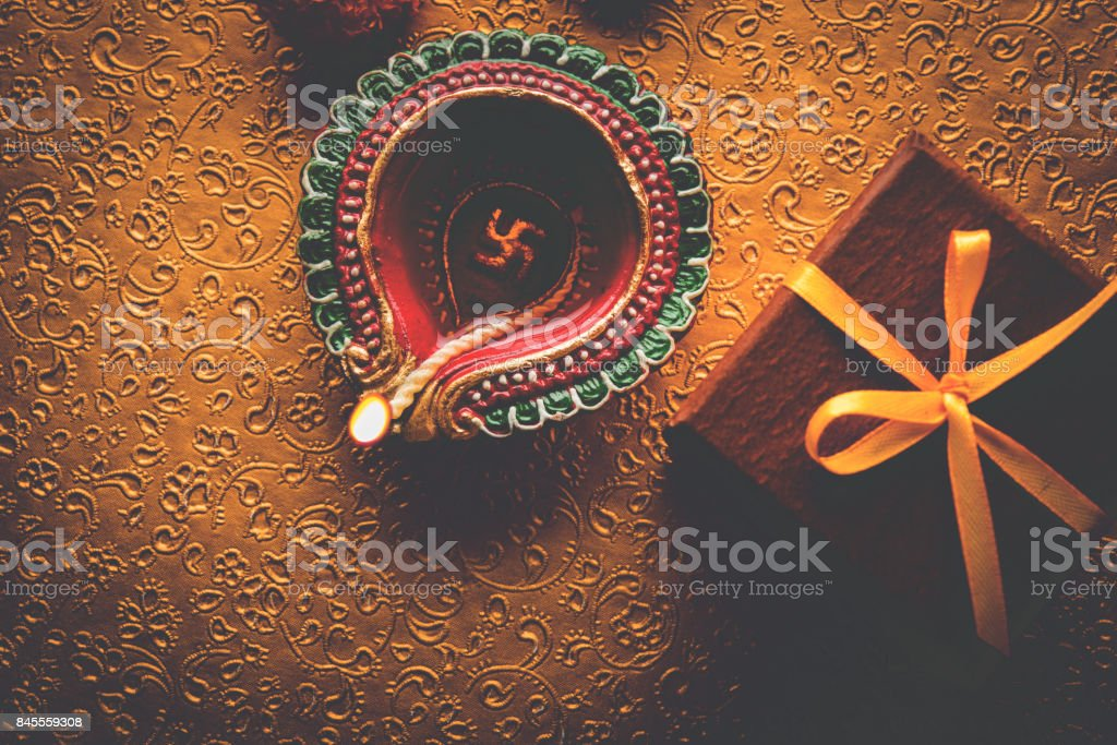 stock photo of beautiful diwali diya with gifts and flowers, over decorative background, moody lighting and selective focus stock photo