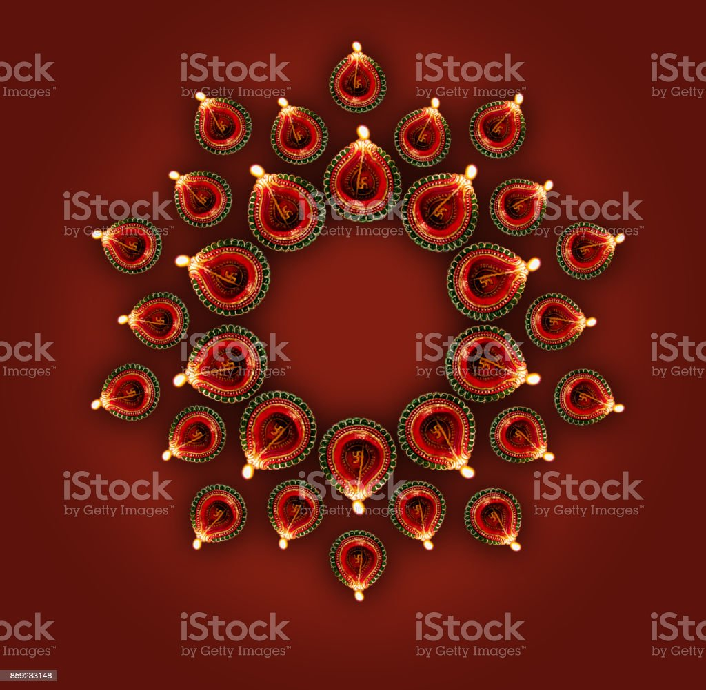 Stock photo of diwali greeting card showing top view of illuminated diya or oil lamp or panti forming a design or rangoli copy space and with Happy Diwali text stock photo