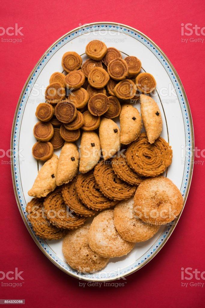 stock photo of Indian festival or diwali food called Bakarvad , karanji or Gujiya, Chakli or Murukku and Anarsa, selective focus stock photo