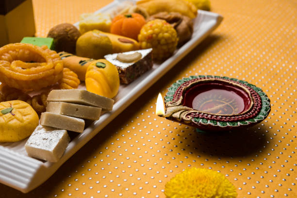 stock photo of indian sweet or mithai and oil lamps or diya with flowers on decorative or colourful background, selective focus - diwali stock pictures, royalty-free photos & images