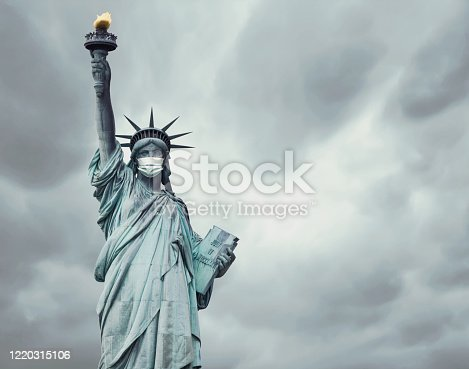 Stock photo of the New York's Statue of Liberty with a mask on its face caused by the coronavirus covid-19 and copy space on the right