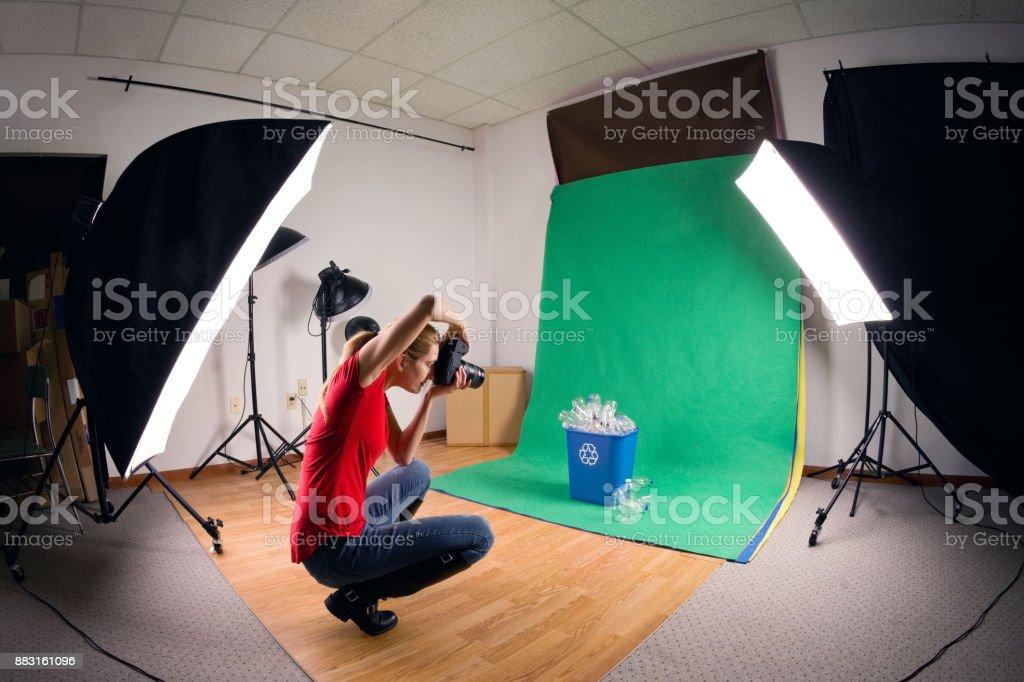 Stock Photographer Taking Studio Photos A photographer taking photos of a recycling bin in her studio. 45-49 Years Stock Photo