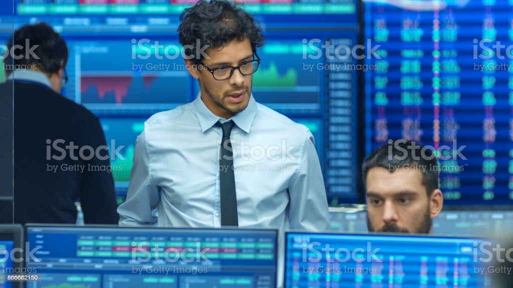 Stock Trader Inspects Others Work and Chat with Other. Busy Office with Multi-Ethnic Team of Brokers, Dealers. Displays Show Numbers and Infographics. stock photo