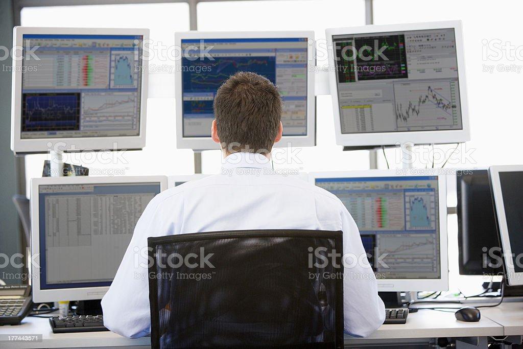 Stock Trader Looking At Multiple Monitors stock photo
