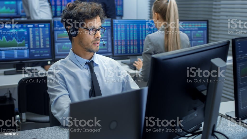 Stock Trader Making Sales with a Headset. In the Background Stock Exchange Office and Group of Traders Working at their Workstations. Stock Trader Making Sales with a Headset. In the Background Stock Exchange Office and Group of Traders Working at their Workstations. Trader Stock Photo