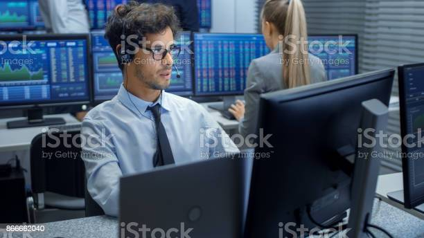 Stock Trader Making Sales With A Headset In The Background Stock Exchange Office And Group Of Traders Working At Their Workstations Stock Photo - Download Image Now