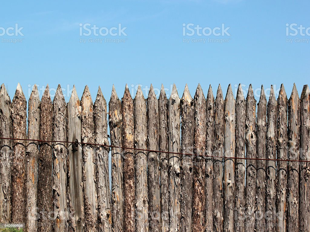 Stockade wooden fence on blue sky background stock photo