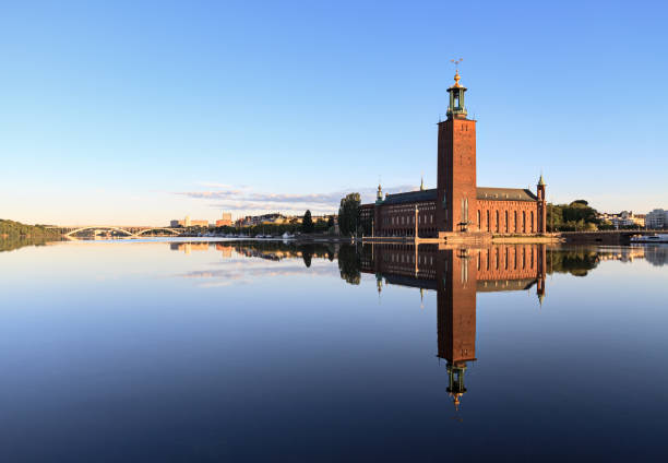 Stockholm City Hall with reflection on calm water Stockholm City Hall with reflection on water at morning stockholm stock pictures, royalty-free photos & images