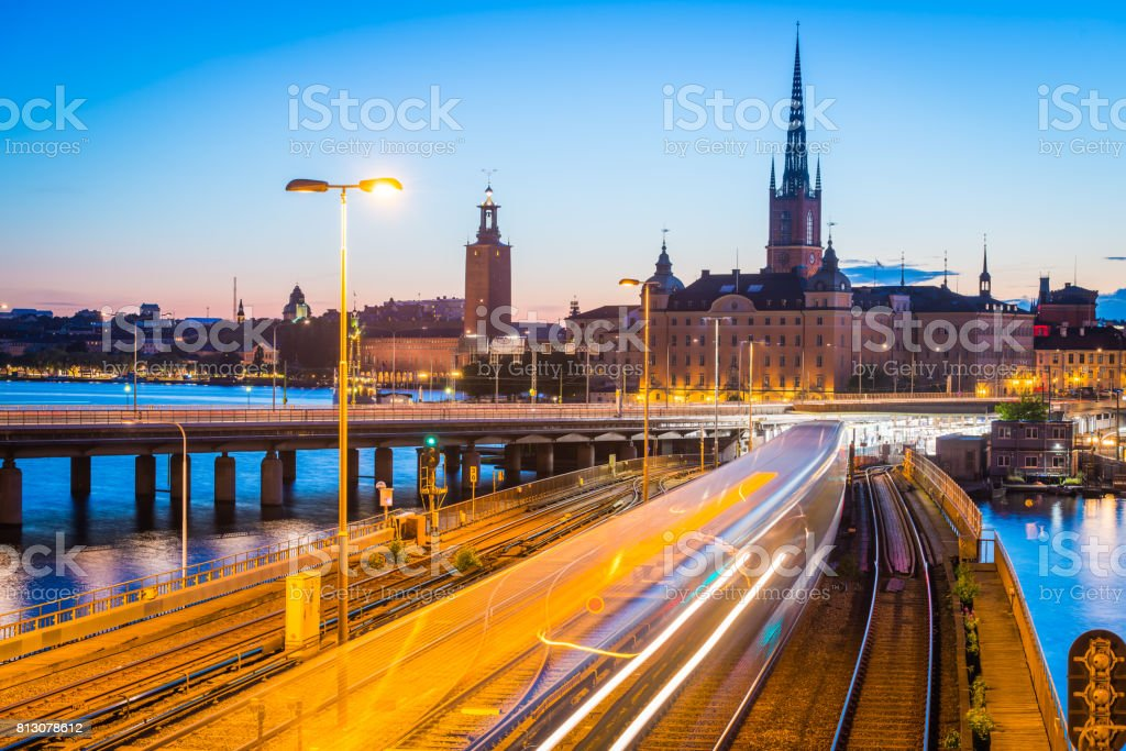 Stockholm commuter train zooming through Gamla Stan illuminated dusk Sweden stock photo
