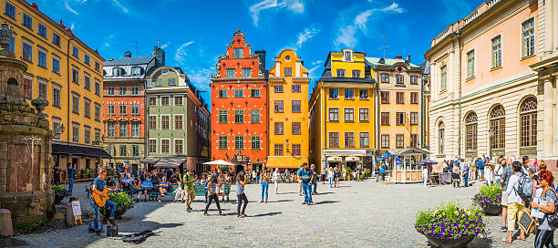 Stockholm Stortorget tourists in medieval square colourful houses restaurants Sweden Stockholm, Sweden - July 9, 2016: Crowds of tourists and locals enjoying the summer sunshine beneath the colourful townhouses and quaint restaurants of historic Stortorget, Great Square, the iconic landmark plaza on Gamla Stan in the heart of Stockholm, Sweden's vibrant capital city. Composite panoramic image created from six contemporaneous sequential photographs. stockholm stock pictures, royalty-free photos & images