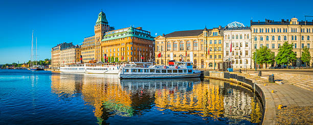 stockholm summer sunrise on nybroviken harbour hotels ferries panorama sweden - stockholm bildbanksfoton och bilder