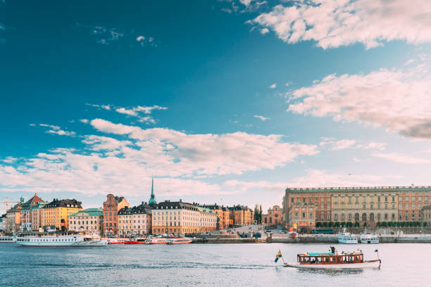 Stockholm, Sweden. Touristic Boat Floating Near Famous Embankment In Old Town Gamla Stan In Summer Evening. Famous Popular Destination Scenic Place And UNESCO World Heritage Site stock photo
