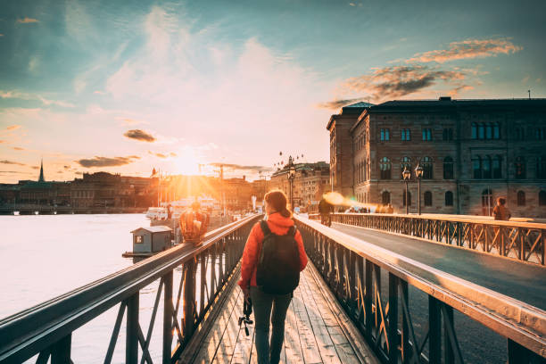 Stockholm, Sweden. Young Caucasian Woman Lady Tourist Traveler Walking On Famous Skeppsholmsbron - Skeppsholm Bridge. Popular Place, Landmark  And Destination In Stockholm, Sweden stock photo
