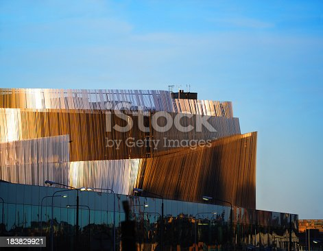 A brand new landmark in central Stockholm, illuminated by colorful sunset against clear blue sky.